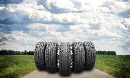 tire cover: Wedge of new car wheels on road stretches into the distance. Roadsides and green grass field. Sky with clouds in background Stock Photo