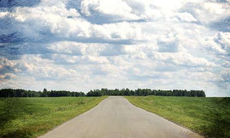 field and sky: Antigua carretera se extiende en la distancia. En los bordes de los caminos y campo de hierba verde. Cielo con nubes en el fondo