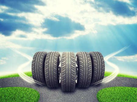 vulcanization: Wedge of new car wheels. Road fork  and green grass field. Sky with clouds and sun beams in background