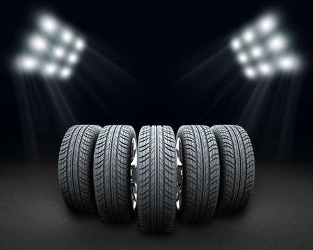 vulcanization: Wedge of new car wheels. Dark grey background with spotlight