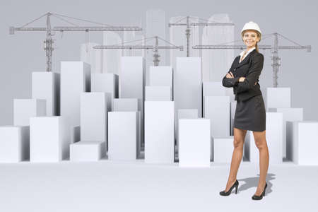 Business woman in suit and helment. Many white cubes with wire-frame buildings and tower cranes on gray background