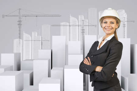 Business woman in suit and helment with crossed arms, looking at camera, smiling. Many white cubes with wire-frame buildings and tower cranes on gray background photo