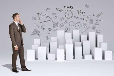 Businessman in suit thinks. Many white cubes with business sketches on gray background