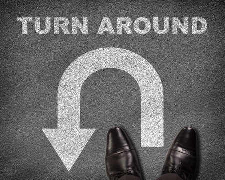 u turn sign: Top view of shoes standing on asphalt road with U-turn sign and text turn around. Business concept Stock Photo