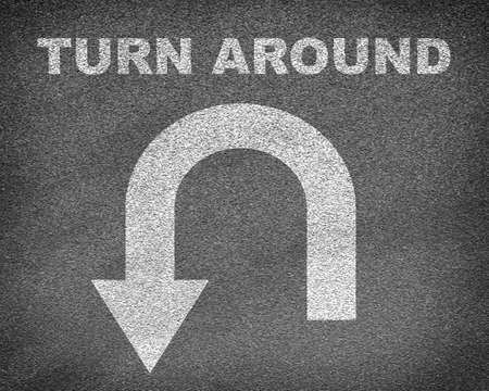 marking up: Asphalt road texture with U-turn sign and text turn around. Business concept