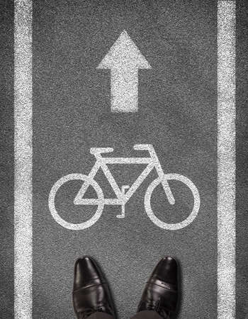 Top view of shoes standing on asphalt road with two line and bicycle sign. Business concept photo