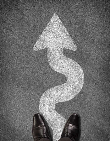 meanders: Top view of shoes standing on asphalt road with winding arrow. Business concept
