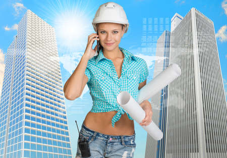 Beautiful girl builder in helmet holding paper scrolls and talking on phone. Two skyscrapers and world map as backdrop