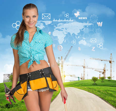 toolbelt: Beautiful girl builder in toolbelt holding tools, looking at camera, smiling. Green hills, road, tower cranes and flying virtual elements as backdrop Stock Photo