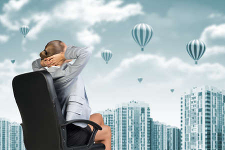 scrunchy: Businesswoman sitting backwards on chair relaxed and put hands behind her head. Building as backdrop