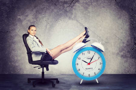 Businesswoman sits in chair, looking at camera. Put your feet up on big red alarm clock. Concrete background photo