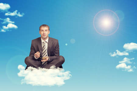 Businessman sitting in lotus position on cloud, holding golden lamp of Aladdin. Sky with sun as backdrop photo