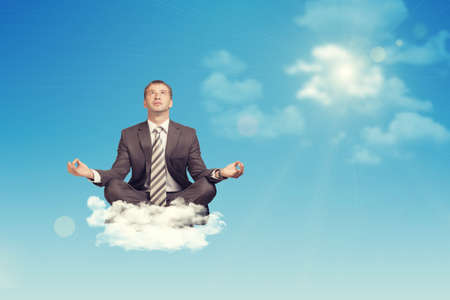 Businessman sitting in lotus position on cloud, looking up. Sky with sun as backdrop photo