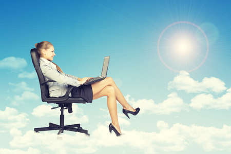 Beautiful businesswoman in suit sitting on office chair and holding open laptop, leaning back, smiling