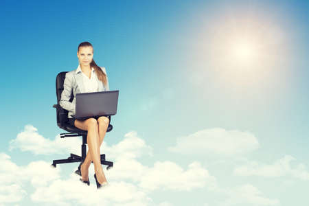 Beautiful businesswoman in suit sitting on office chair and holding open laptop, leaning back, smiling. Front view photo