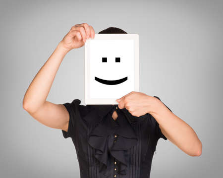 Girl in black dress covered her face with tablet. On screen code smiley. Gray background photo