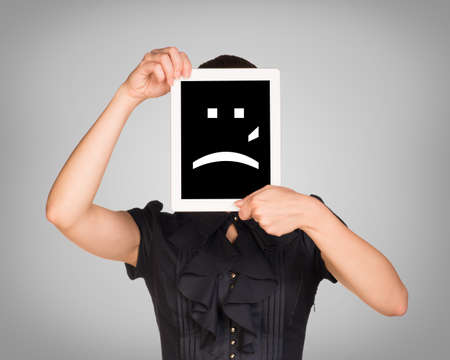 sad smiley: Girl in dress covered her face with tablet. On screen sad smiley. Gray background