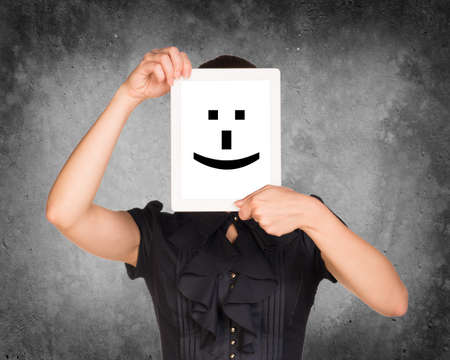 Girl in dress covered her face with tablet. On screen cheerful smiley. Concrete background photo