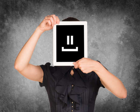 Woman in black dress covered her face with tablet. On screen code smiley. Concrete background photo