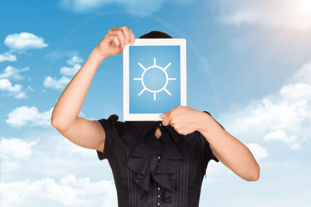 sun screen: Girl in dress covered her face with tablet. On screen sun symbol. Blue sky with clouds as backdrop