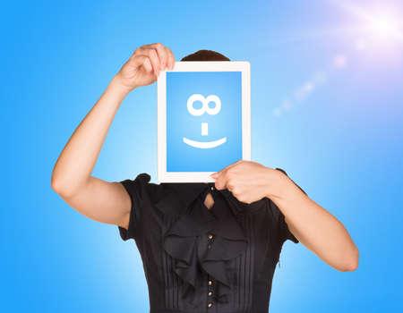 cara sonriente: Chica en vestido se cubri� la cara con la tableta. El c�digo de pantalla sonriente. Cielo azul con la luz del sol como tel�n de fondo Foto de archivo