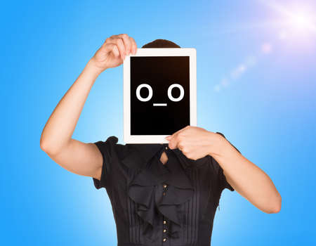 sun screen: Young girl in black dress covered her face with tablet. On screen surprised smiley. Blue sky with sun light as backdrop Stock Photo