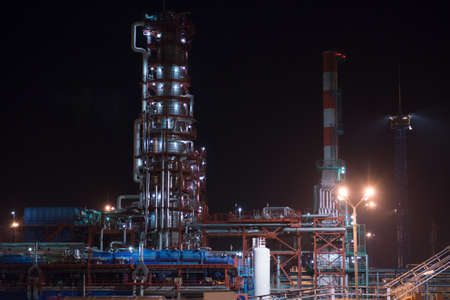 distillation: Industrial area refinery. Distillation column and pipes. Night view Stock Photo