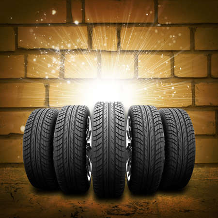 tire cover: Car wheels. Abstract background is brick wall, concrete floor and light at center.