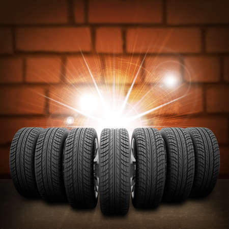 Wedge of new car wheels. Abstract background is red brick wall, concrete floor and light at center photo