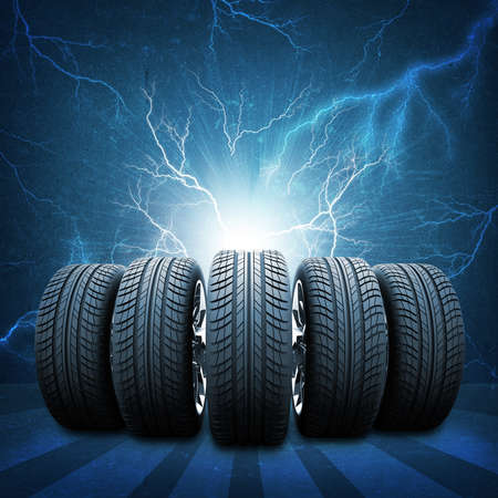 Five of new car wheels. Abstract background is concrete wall, lightning and stripes at bottom