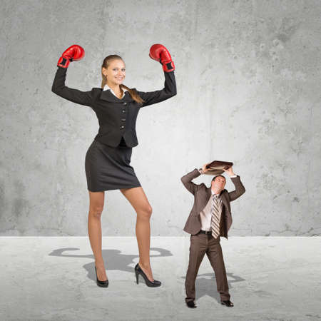 cowering: Successful businesswoman flexing her powers in a conceptual image of a giant business woman wearing boxing gloves towering over a cowering businessman sheltering under his briefcase