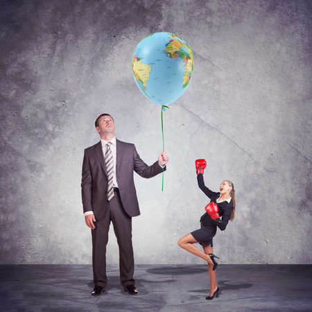 short gloves: Conceptual Businessman Holding and Looking at the Balloon, with World Map Print, with a Small Businesswoman Posing in Boxing Gloves on the Side. Captured in Studio with Weathered Wall Background