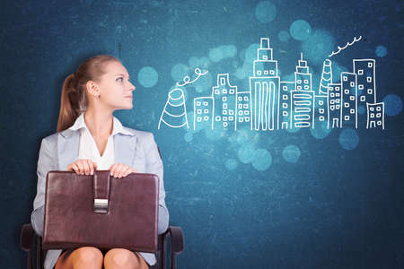 aspirational: Young Businesswoman Sitting in Chair with Briefcase in Lap, Looking to the Side at Illustration of City Skyline in Aspirational Concept Image