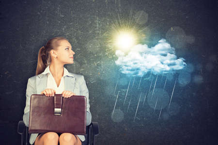 aspirational: Young Businesswoman Sitting in Chair with Briefcase in Lap, Looking to the Side at Illustration of Weather in Aspirational Concept Image