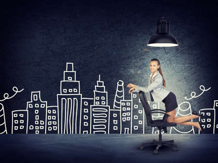 aspirational: Portrait of Young Businesswoman Kneeling on Office Chair Beneath Overhead Light in front of Illustration of City Skyline in Aspirational Concept Image