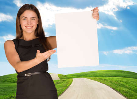 constraction: Young woman holding blank poster with nature on background. Place for constraction