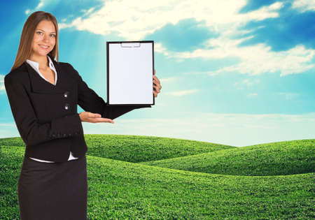 feild: Young woman holding paper holder with nature on background. Green feild and blue sky Stock Photo