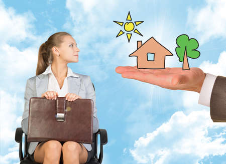 young woman sitting: Businessmans hand holding an illustration of house with tree and sun and offering to young woman sitting in chair Stock Photo