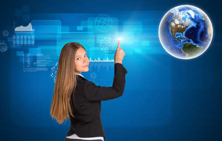 looking in corner: Businesswoman standing back and looking at camera pressing on holographic screen with graphical charts. Earth in upper right corner.  Stock Photo