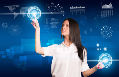 Young woman pressing buttons using two hands and looking up at right hand social network future interface, pressing light point on holographic screen. Social network concept photo