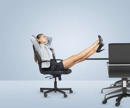 crossing legs: Businesslady sitting in chair with her hands behind head. Looking up and crossing legs Stock Photo