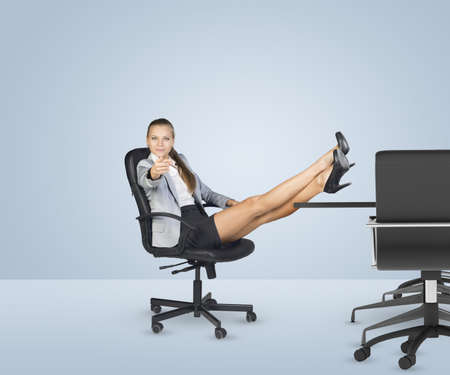 Businesslady sitting in the chair with her crossed legs on table and fingering at camera on white background Stock Photo