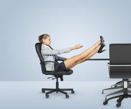 Businesslady sitting profile in chair with her crossed legs on table and with arms extended forward. Business office photo