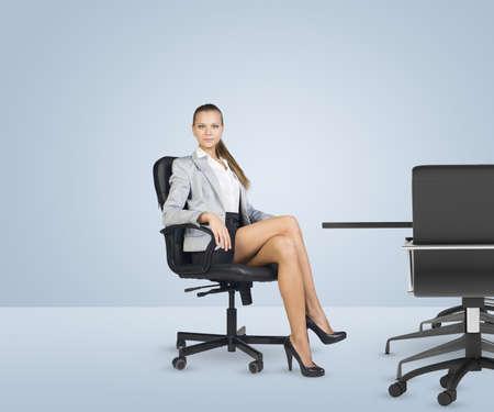 skirts: Businesslady sentado media vuelta en la silla con las piernas cruzadas y mirando a la cámara sobre fondo blanco. Negocios en el cargo. Foto de archivo