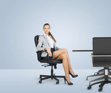 Businesslady sitting half-turned in chair with her crossed legs and looking at camera on white background. Business office.