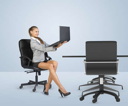 Businesslady sitting half-turned in chair and looking at laptop in her hands. Business centre photo