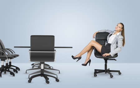 Busineswoman sitting on chair relaxing and looking at camera. White background Stock Photo