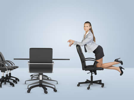 busineswoman: Busineswoman kneeling on chair and looking at camera. Business centre Stock Photo