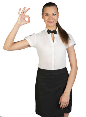 okay: Portrait of young waitress showing sign okay and looking at camera. Isolated background