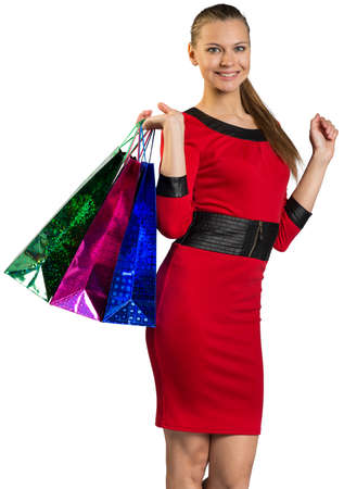 half turn: Half-turned young woman with teeth smile handing colorful shopping bags and looking at camera.
